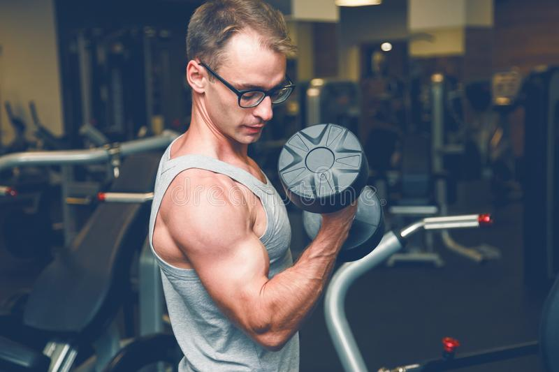 Muscular bodybuilder guy doing exercises with dumbbell. stock photo