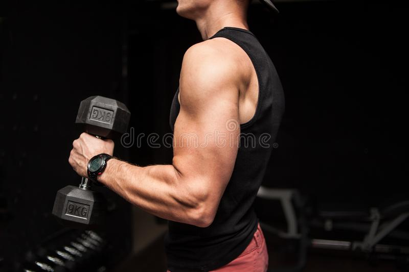 Muscular bodybuilder guy doing exercises with dumbbell over black background stock photo