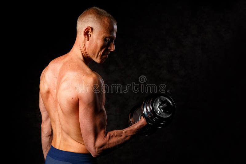 Muscular bodybuilder guy doing exercises with dumbbell over black background royalty free stock photography
