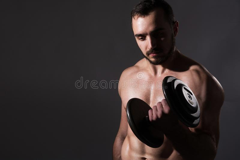 Muscular bodybuilder guy doing exercises with dumbbell stock photography