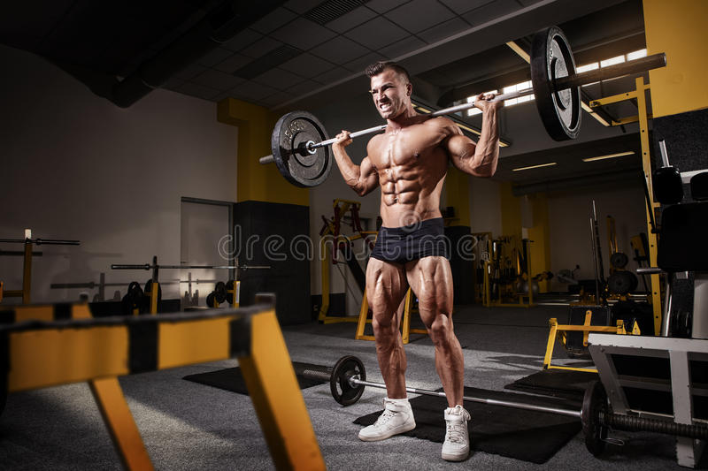 Muscular bodybuilder guy doing exercises with dumbbell. In yellow gym stock photos