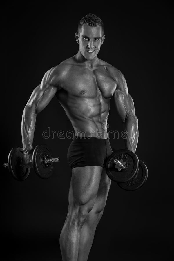 Muscular bodybuilder guy doing exercises with dumbbells. Over black background stock photography