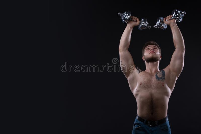 Muscular bodybuilder guy doing exercises with dumbbells over black background royalty free stock photography