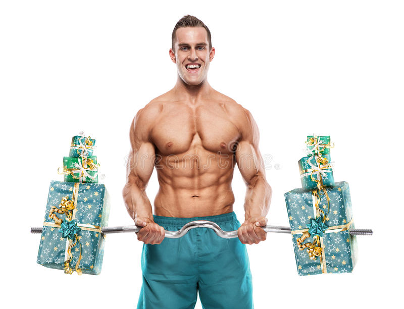 Muscular bodybuilder guy doing exercises with gifts over white b royalty free stock photography