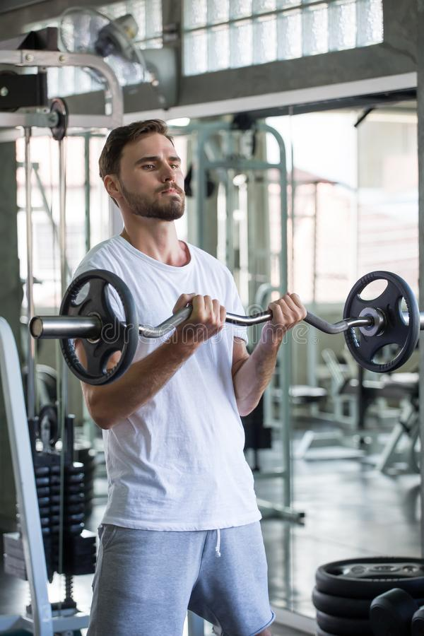Muscular bodybuilder guy doing exercises with weight lifting barbell  in gym . sport young fitness man training .work out healthy royalty free stock photo