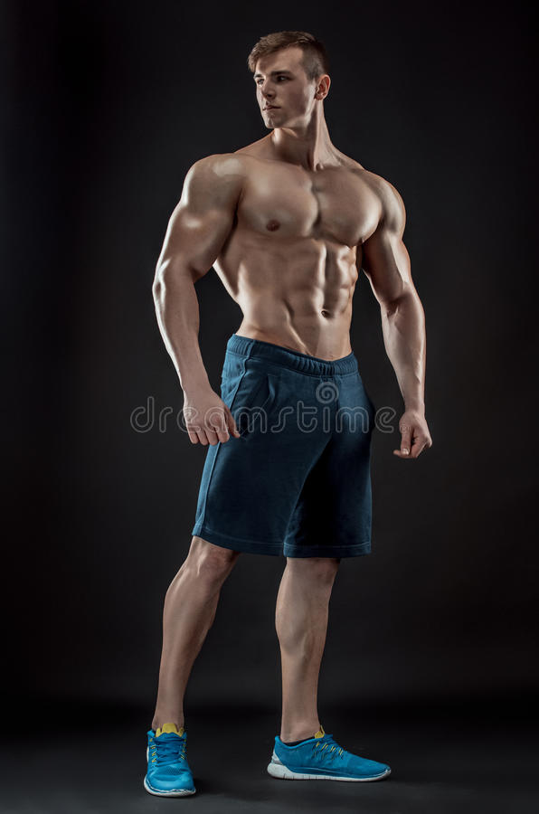 Muscular bodybuilder guy doing posing over black background stock photos