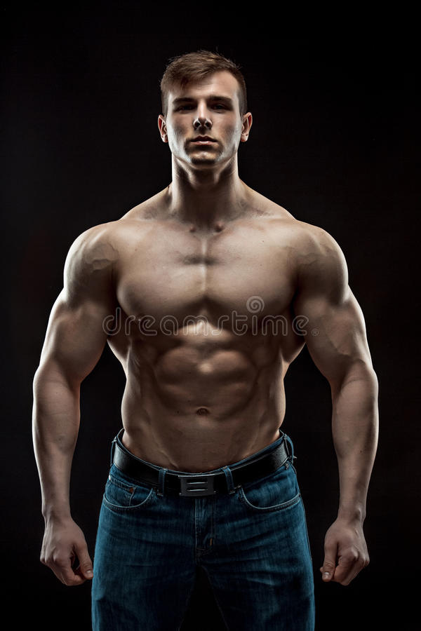 Muscular bodybuilder guy doing posing over black background royalty free stock photo