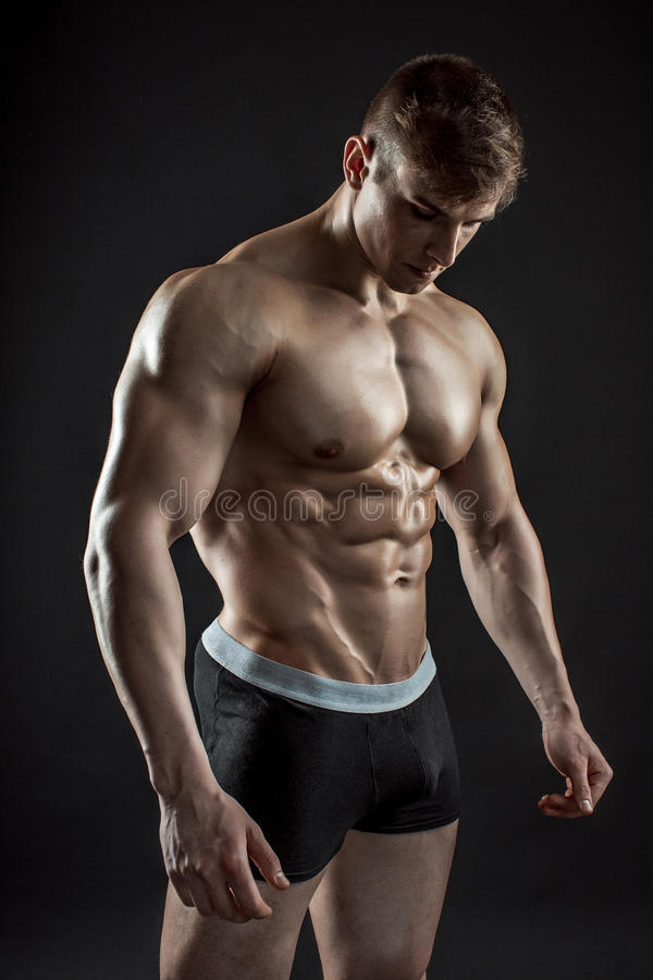 Muscular bodybuilder guy doing posing over black background stock photography