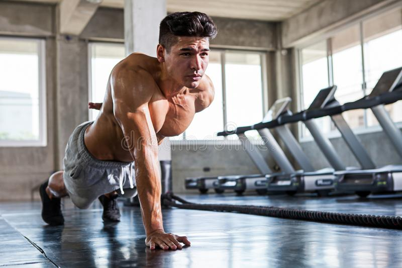 Muscular bodybuilder guy doing push ups one hand exercise in fi. Tness gym . Shirtless young sport man training royalty free stock photography