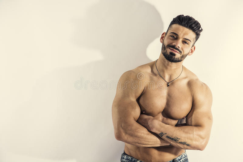 Muscular bodybuilder leaning against white wall royalty free stock image