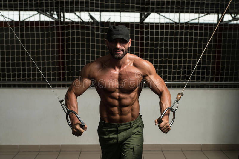 Muscular Bodybuilder Performing Cable Crossover. Mature Bodybuilder Is Working On His Chest With Cable Crossover In A Dark Gym stock image
