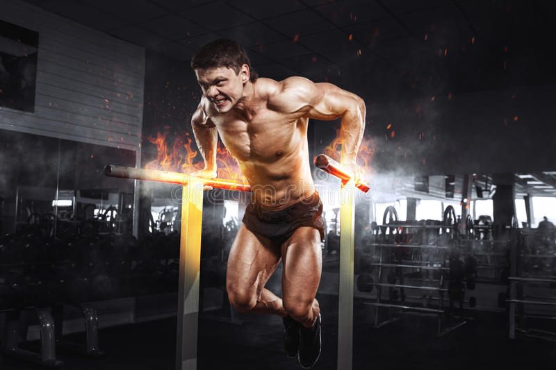Muscular bodybuilder working out in gym doing exercises on burning fire parallel bars. Concept sport stock images