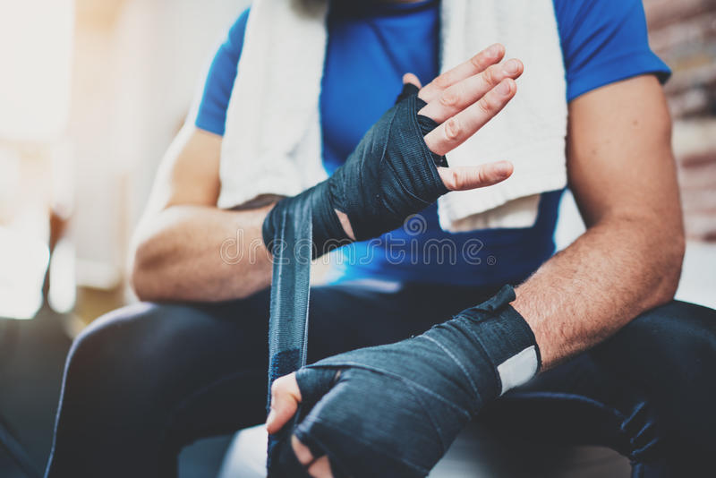 Muscular Boxer man prepairing hands for hard kickboxing training session in gym. Young athlete tying black boxing stock photos