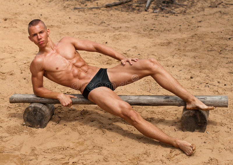 Muscular boy on beach stock image