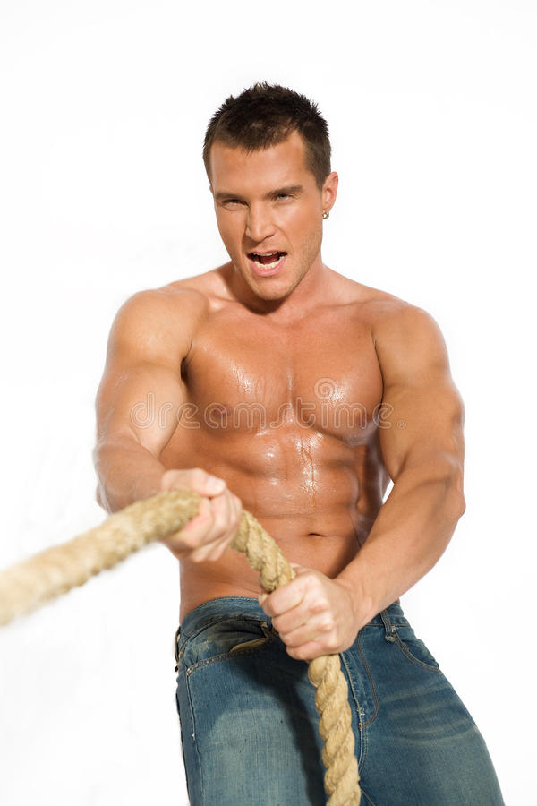 Muscular builder man pulling rope stock images
