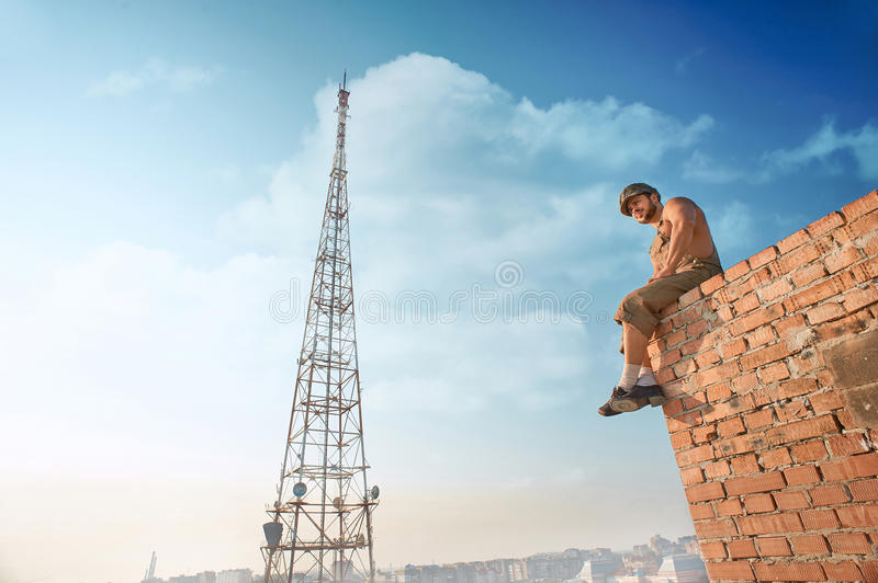 Muscular builder standing on brick wall on high. stock photo