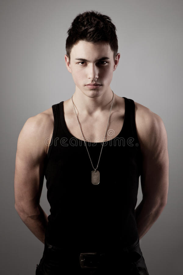 Muscular built man with a dog tags. stock photos