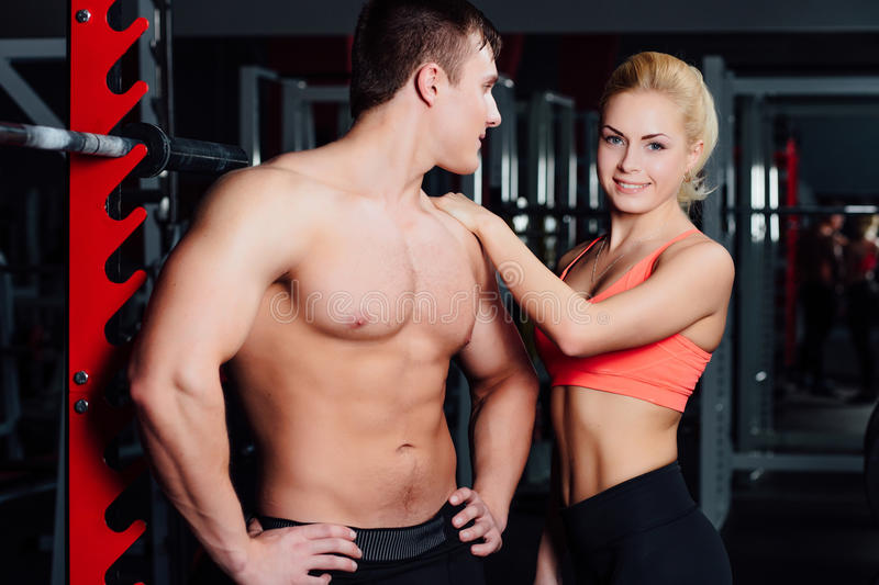 Muscular couple discussing together with arm on shoulder stock photography