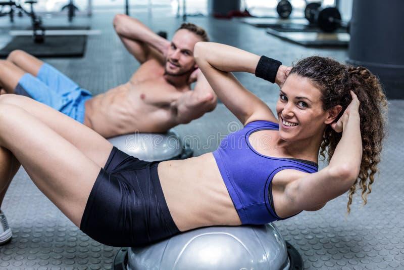Muscular couple doing bosu ball exercises stock photos