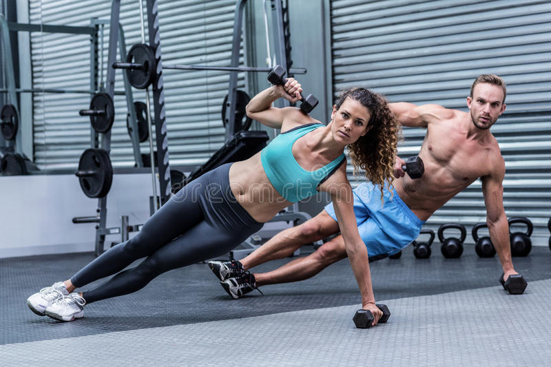 Muscular couple doing side plank royalty free stock photography