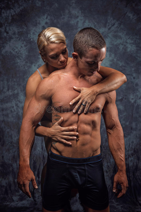 Muscular couple embracing. Young fit, attractive, muscular couple embracing with grey studio background stock photo
