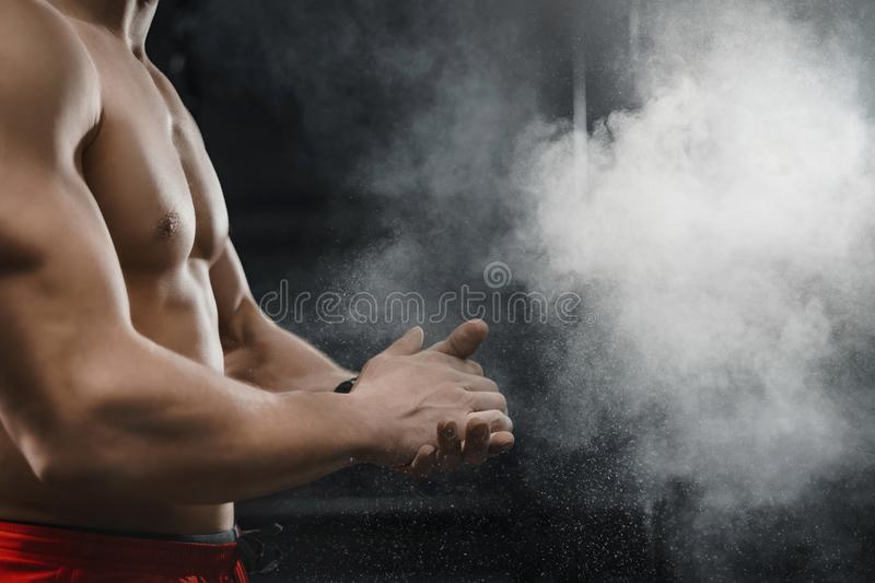 Muscular crossfit athlete clapping hands and preparing for workout at the gym. Cloud of dust chalk powder on dark background. Sport concept. Copy space stock image