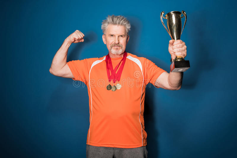 Muscular elderly man holding trophy and showing biceps royalty free stock image
