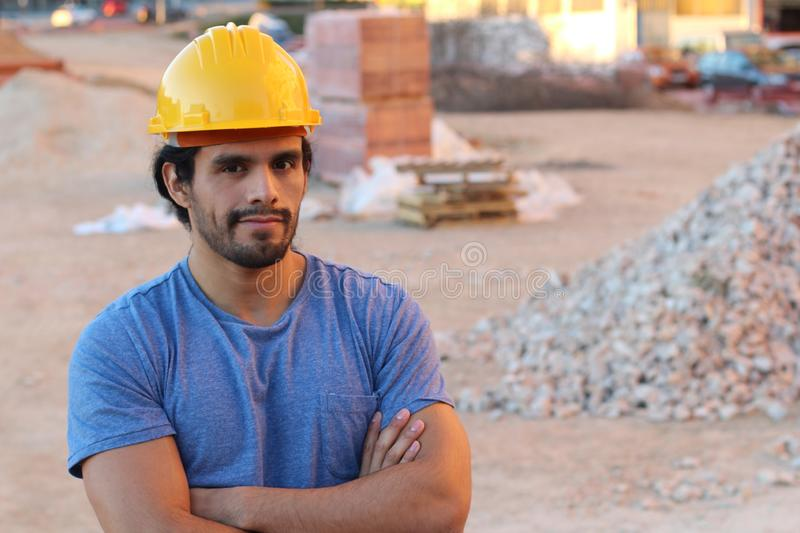 Muscular ethnic construction worker with arms crossed stock image