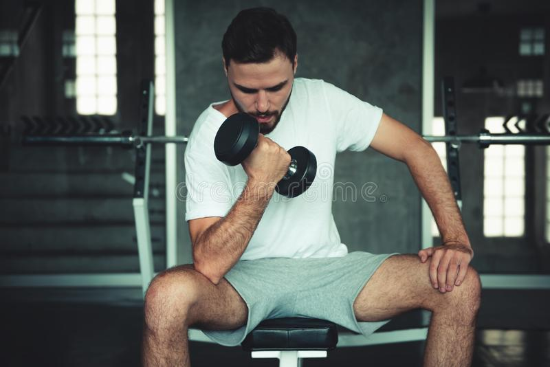 Muscular exercises dumbbell bodybuilder in fitness gym of sportsman., Portrait of caucasian handsome man doing weightlifting and stock image