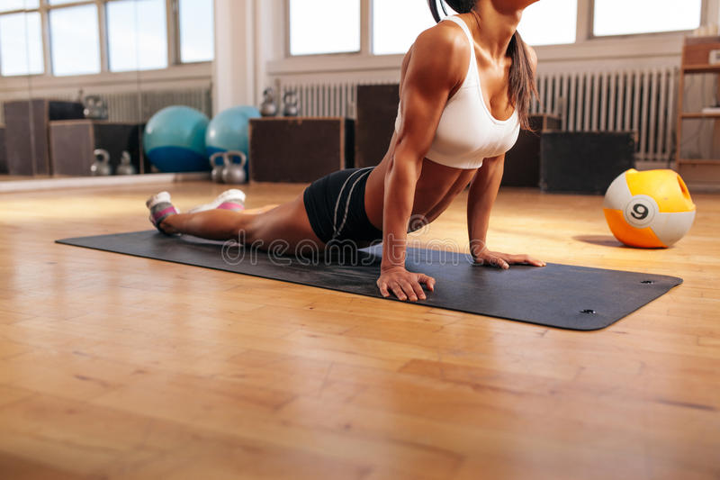 Muscular female doing stretching exercise in gym royalty free stock image