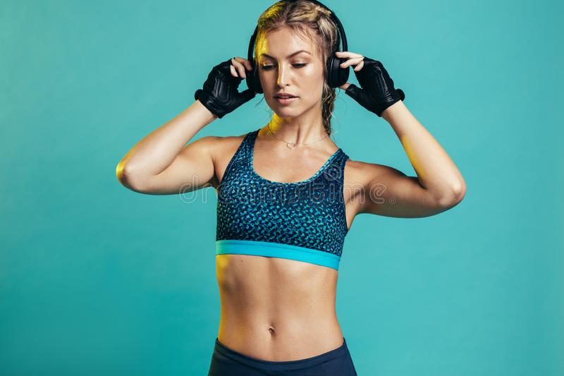 Muscular female with headphones stock image