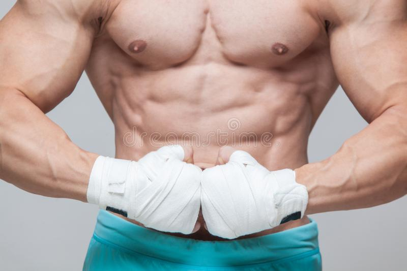 Muscular Fighter kickbox With white Bandages against the grey background.  stock image