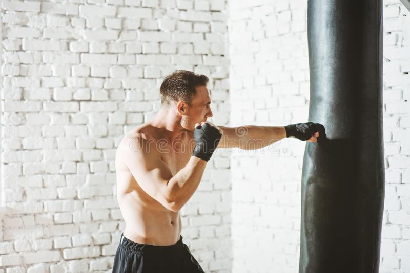 Muscular fighter practicing with punching bag against white brick wall. royalty free stock photo