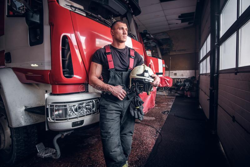 Muscular fireman holding a protective helmet in a garage of a fire department stock images