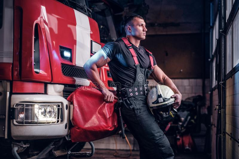 Muscular fireman holding a protective helmet in a garage of a fire department royalty free stock image