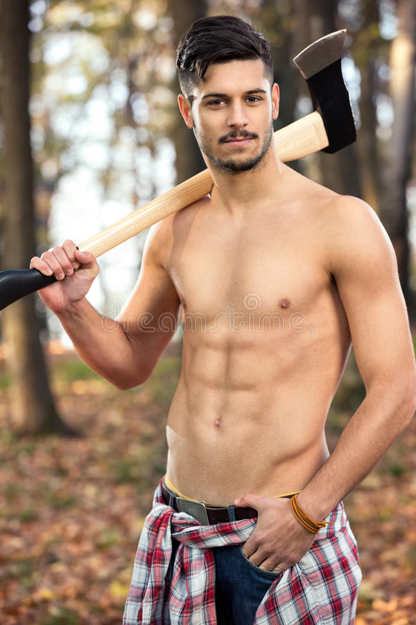 Muscular fit lumberjack. Posing with axe stock photo