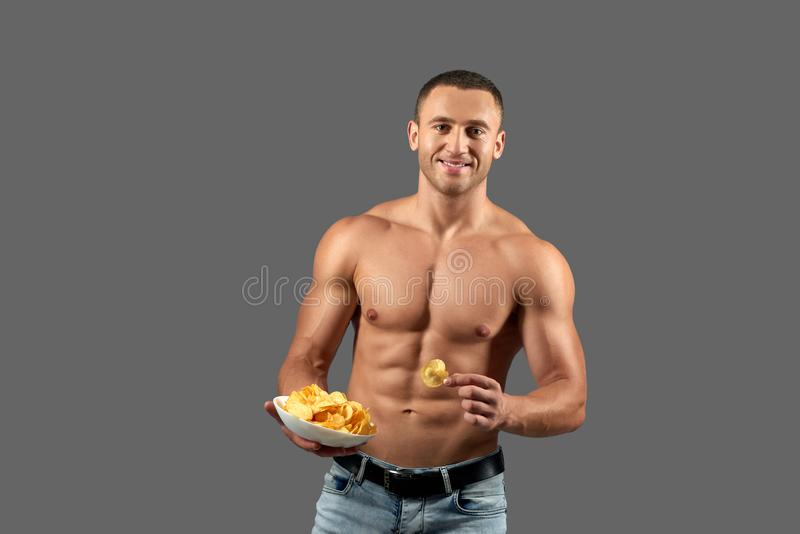 Attactive man smiling, holding bowl with chips. stock photos