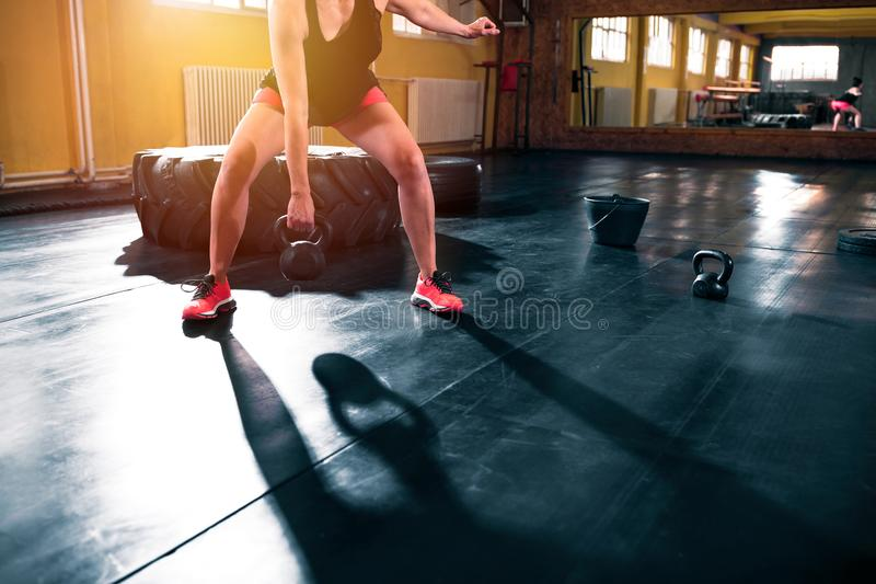 Muscular fit woman doing workout with kettlebell in gym. Muscular fit woman doing hard intensive workout with kettlebell in gym royalty free stock images