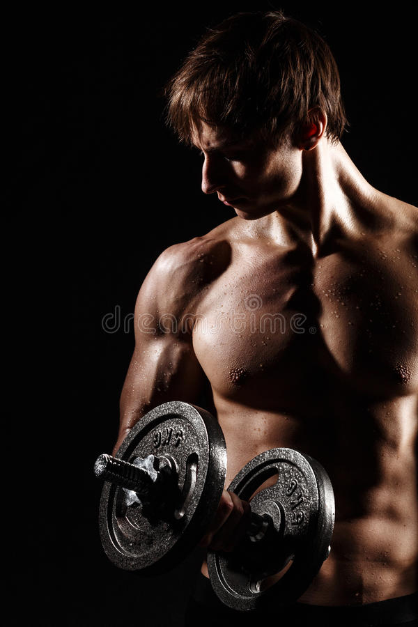 Muscular and fit young bodybuilder fitness male model posing over black background with DUMBBELL. Perfect fitness WET body with D royalty free stock image
