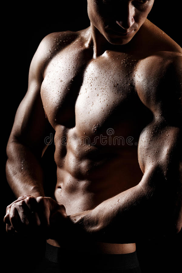 Muscular and fit young bodybuilder fitness male model posing over black background. Perfect fitness WET body with DROPS. Ideal royalty free stock photography