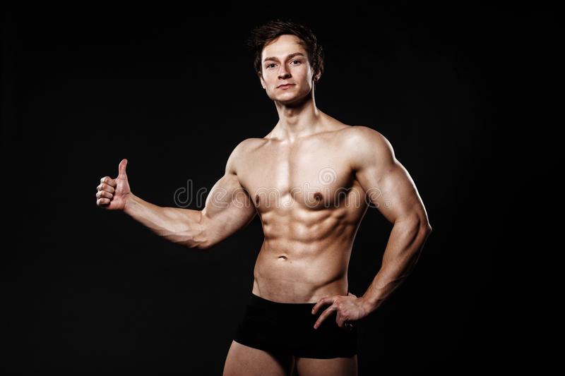 Muscular and fit young bodybuilder fitness male model showing th stock images