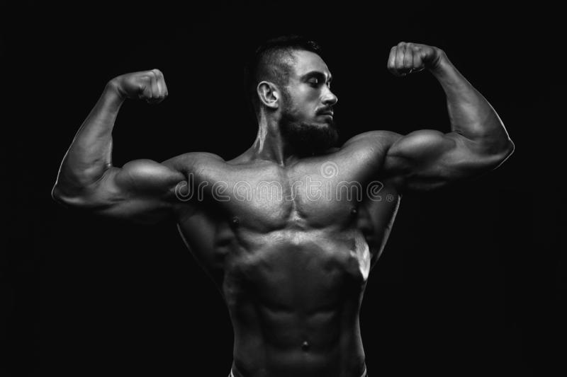 Muscular fitness burnet beard man is showing biceps on black background. BW royalty free stock photography