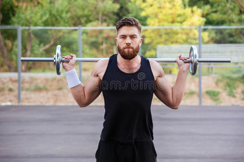 Muscular fitness handsome man workout with barbell royalty free stock photography