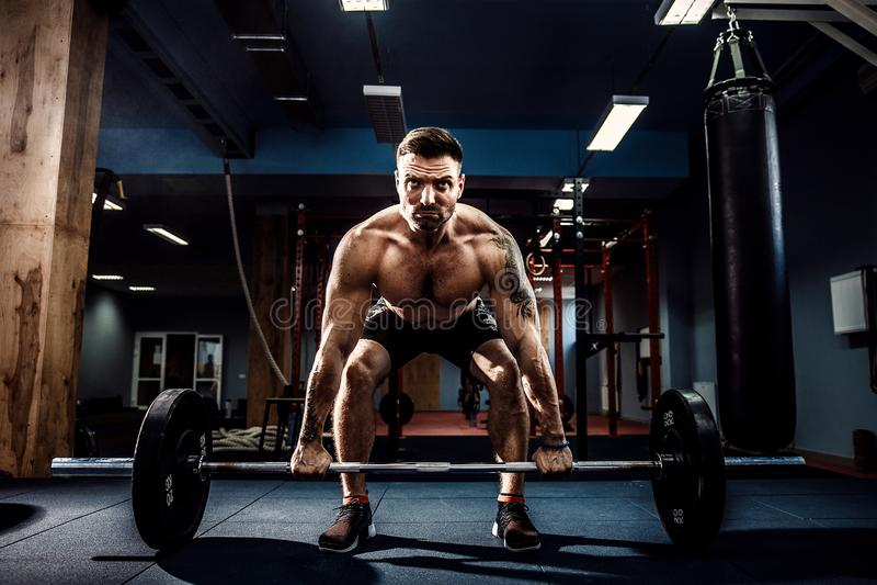 Muscular fitness man doing deadlift a barbell in modern fitness center. Functional training. stock photos