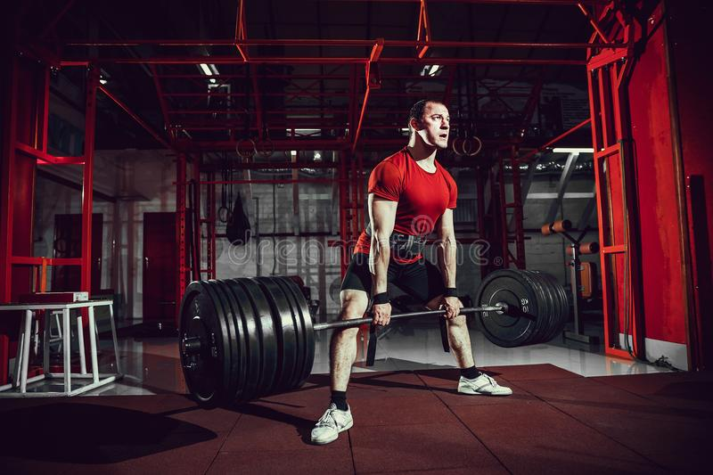 Muscular fitness man doing deadlift a barbell in modern fitness center. Functional training. royalty free stock images