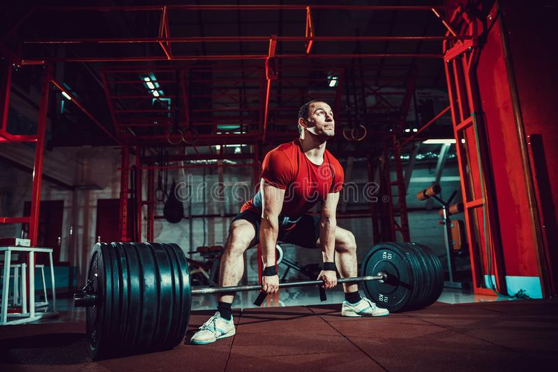 Muscular fitness man doing deadlift a barbell in modern fitness center. Functional training. royalty free stock image