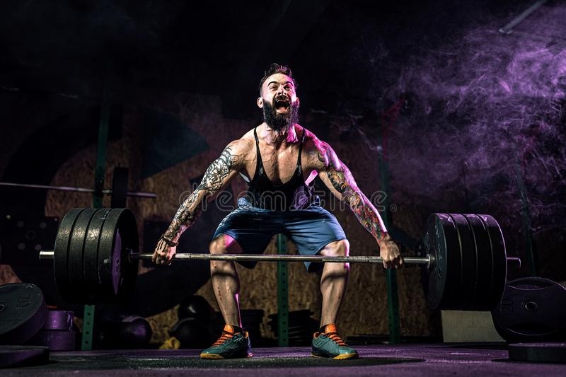 Muscular fitness man doing deadlift of a barbell in modern fitness center. Functional training. royalty free stock photo