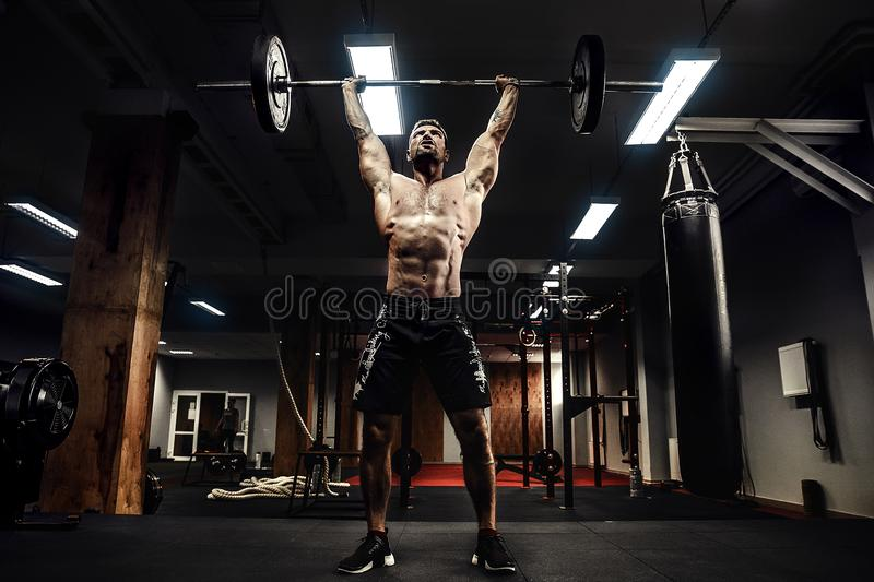 Muscular fitness man doing deadlift a barbell over his head in modern fitness center. Functional training. royalty free stock photos