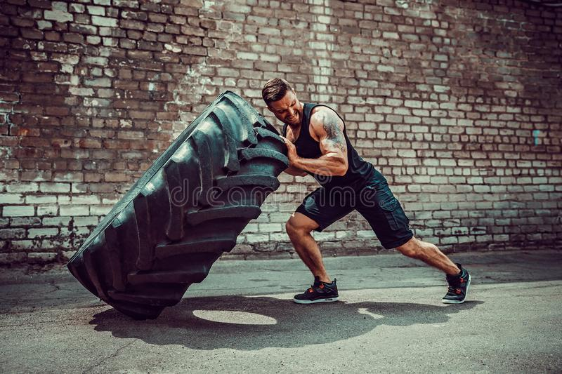 Muscular fitness man moving large tire. royalty free stock images
