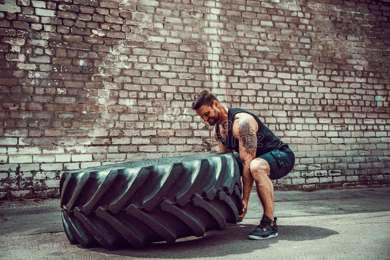 Muscular fitness man moving large tire. stock photos
